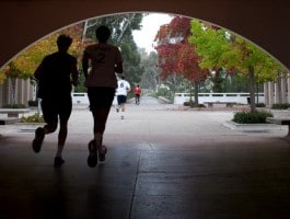 student-jogging-under-bridge